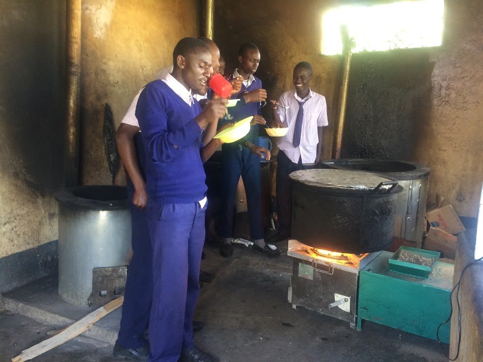 Katumani Secondary Pupils in awe of the stove and eating food prepared using the stove